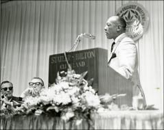 Thumbnail of Jesse Owens presenting at a podium during the National Association of Collegiate Directors of Athletics event, 1960s