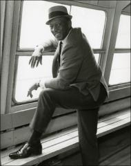 Thumbnail of Jesse Owens poses for a photo next to a window, 1960s