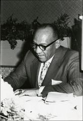 Thumbnail of Jesse Owens signs a paper while sitting at a dining table, 1960s