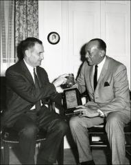 Thumbnail of Jesse Owens and another man hold Jesse's bronzed shoe, 1960s