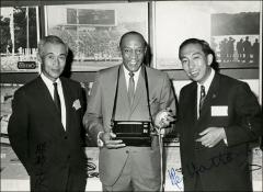 Thumbnail of Jesse Owens poses with two Seiko employees at an event in Japan, 1964