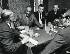 Thumbnail of Jesse Owens dines at a restaurant with a group, 1960s