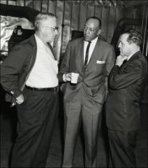 Thumbnail of Jesse Owens talks in a small group, 1964