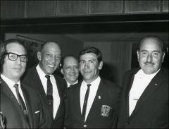Thumbnail of Jesse Owens poses for a photo with four men at an event, 1960s