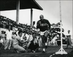 Thumbnail of Jesse Owens prepares to run a race on an outdoor track, 1960s