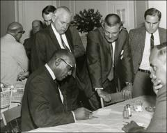 Thumbnail of Jesse Owens signs a paper at a banquet, 1960s