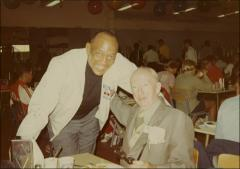 Thumbnail of Jesse Owens poses with a man in a cafeteria, 1960s