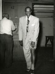 Thumbnail of Jesse Owens poses with his pant leg pulled up, circa 1940s
