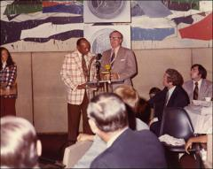 "Thumbnail of Jesse Owens presents jointly with an unidentified man on stage at the ""Great Olympic Moments"" ceremony, 1972"
