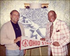 "Thumbnail of Jesse Owens holds an OSU banner with an unidentified man at the ""Great Olympic Moments"" ceremony, 1972"