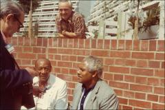Thumbnail of Jesse Owens sits outside in the Olympic Village during an interview, 1972