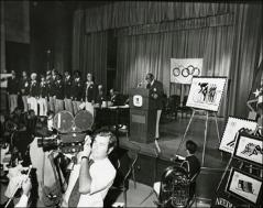 Thumbnail of Jesse Owens speaks behind a podium at the Munich Olympics Postage Stamp presentation, 1972