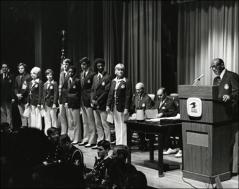 Thumbnail of Jesse Owens speaks on stage for the Munich Olympics Postage Stamp presentation, 1972