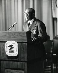 Thumbnail of Jesse Owens speaks behind a podium at the Munich Olympics Postage Stamp presentation, 1972 (vertical view)