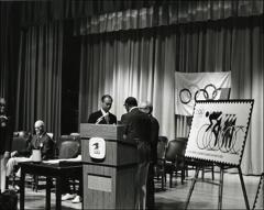 Thumbnail of Jesse Owens talks on stage with two men at the Munich Olympics Postage Stamp presentation, 1972