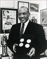 Thumbnail of Jesse Owens poses with his four gold medals, 1972