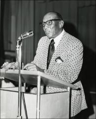 Thumbnail of Jesse Owens speaks on stage during a trip to Dysart Public School, 1973