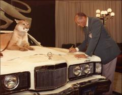 Thumbnail of Jesse Owens signs a showroom car at the Lincoln-Mercury Sports Panel, 1973