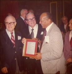 Thumbnail of Jesse Owens holds the Man of the Year Award, 1973