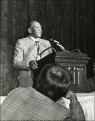Thumbnail of Close up of Jesse Owens behind a podium at the NCAA Honors Luncheon, 1974