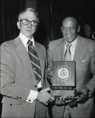 Thumbnail of Jesse Owens holds a plaque with Alan Chapman, 1974