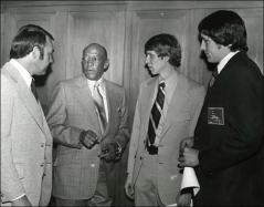 Thumbnail of Dick Enberg, the Master of Ceremonies, Jesse Owens, David Wottle and David Blandino talk during the NCAA Honors Luncheon, 1974