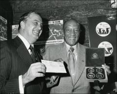 Thumbnail of Jesse Owens poses with Jack Pinyan, US Director of Olympic Coins, 1975