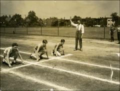 Thumbnail of Jesse Owens works with teenagers at a track, circa 1930s