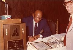 Thumbnail of Jesse Owens signs an autograph at the Motor City Traffic Club, 1979