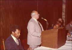 Thumbnail of An unidentified man speaks at a podium during the Motor City Traffic Club, 1979