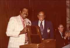 Thumbnail of Jesse Owens poses for a photo with an unidentified man holding an award plaque, 1979