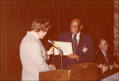 Thumbnail of Jesse Owens receives a framed award at the Motor City Traffic Club ceremony, 1979