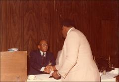 Thumbnail of Jesse Owens shakes hands with a man at the Motor City Traffic Club ceremony, 1979