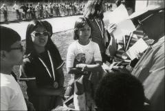 Thumbnail of Jesse Owens signing papers for children at the ARCO Jesse Owens games, 1970s