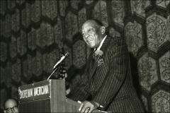 Thumbnail of Jesse Owens presents behind a podium at the Brunswick National Tournament, 1970s