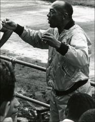 Thumbnail of Jesse Owens talks with children at a race track in Costa Rica, 1970s