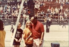 Thumbnail of Jesse Owens talks with two young runners at a track race, 1970