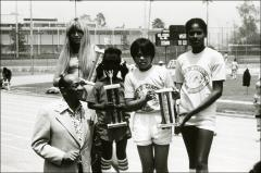 Thumbnail of Jesse Owens poses for a group photo with children holding trophies, 1970s