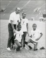 Thumbnail of Jesse Owens poses with three young trophy winners at a track meet, 1970s