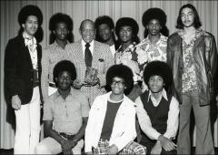 Thumbnail of Jesse Owens poses for a group photo with male students, 1970s