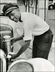 Thumbnail of Jesse Owens adds oil to a car, circa 1930s