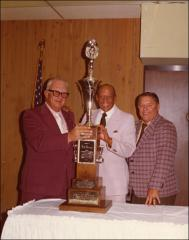 Thumbnail of Jesse Owens stands with two men behind a trophy, 1974