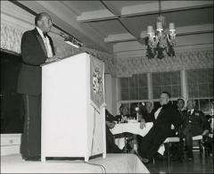 Thumbnail of Jesse Owens gives a speech on stage at a formal dinner event, 1974