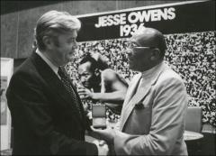 Thumbnail of Jesse Owens holds a medal while shaking hands with a man, 1970s