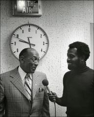 Thumbnail of Jesse Owens talks into a microphone held by a radio host, 1970s