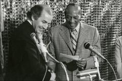 Thumbnail of Jesse Owens shakes hands with another man while they both stand in front of a podium, 1970s