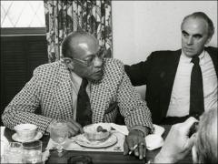 Thumbnail of Jesse Owens eats and smokes during a meeting, 1977-78