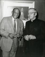 Thumbnail of Jesse Owens poses for a photo with a priest, 1970s