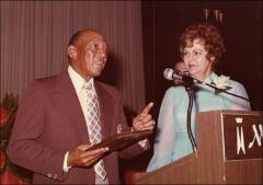 Thumbnail of Jesse Owens holds a plaque next to a woman on stage, 1970s