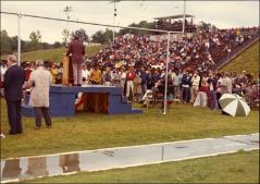 Thumbnail of Jesse Owens gives a speech at a high school stadium (view from behind), 1970s